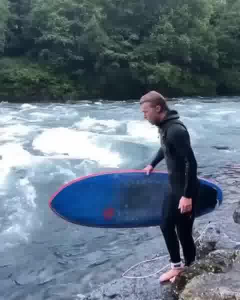 Surfing a river break in Norway